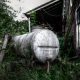 an old dirty white water tank abandoned in the middle of wild plants and a house